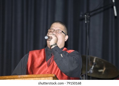 BRONX, NY - APRIL 9: Pentecostal Christian singer Hector Delgado sings during Christian concert event held at Lehman High School. Taken April 9, 2011 in the County of the Bronx, NY.