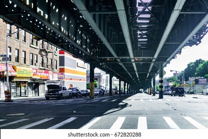 Bronx, USA - June 11, 2017: Road and street under subway railroad with restaurants and shops with sidewalk in downtown Fordham area