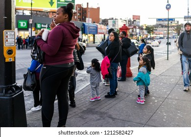 Bronx, USA - October 27, 2017: People family waiting to cross street in Fordham Heights center, New York City, NYC in evening