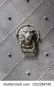 Bronz lion head door knob on an old iron gate with studs