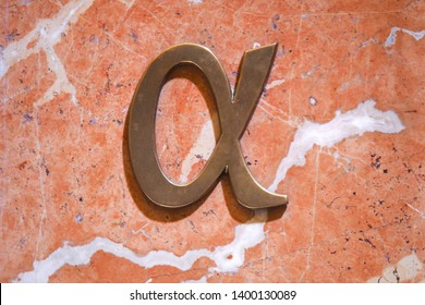 A bronze Alpha symbol on pink marble