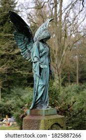 Bronze angel statue in a graveyard, green patina, oxidation