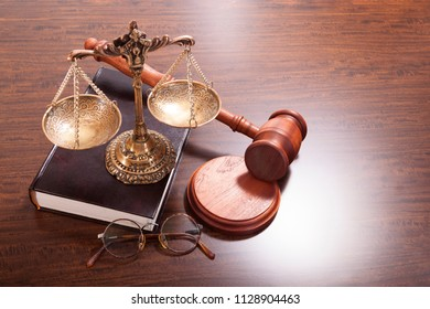 Bronze antique scales, judge hammer, round glasses and a book on the table