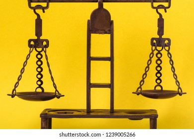 bronze antique scales on a yellow background, symbol of justice