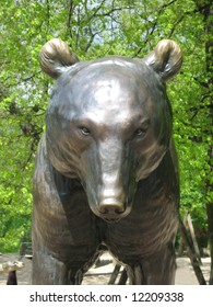 Bronze bear statue with reflection in nature