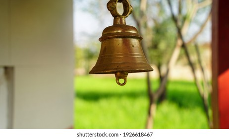 Bronze bell in indian temple in the green crops blur background. Hindu temple brass bell hanging in gold color