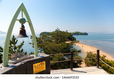 """A bronze bell on the viewpoint atop """"Hill of Commitment, Lovers' Sanctuary"""" overlooking the Angel Road, a tidal sandbar and a famous tourist attraction in Tonosho, Shodoshima Island, Kagawa, japan"""