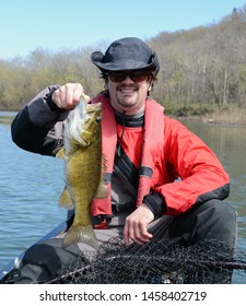 A bronze and brown smallmouth bass being held vertically by a smiling man in a drysuit on a river on a sunny early spring day