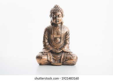 A bronze buddha indoor souvenir statue in lotus position isolated on a plain white background and surface.