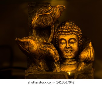bronze colored idol of lord buddha, spot lit and isolated on a dark background. Eyes closed in meditation. Idol is placed on the right side of the image and there is an empty copy space on the left.