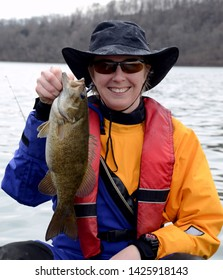 A bronze colored smallmouth bass being held vertically by a smiling woman in a drysuit on a river on a cloudy day