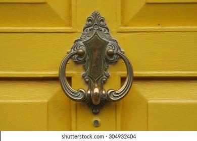bronze door knocker on a yellow door