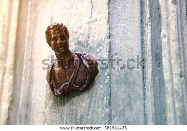 Bronze doorknob in the shape of male bust set on old cracked door painted in light blue color.