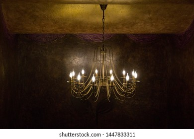 Bronze electric chandelier on the ceiling. Imitation of antiquity.