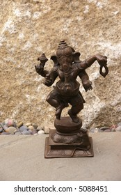 Bronze Ganesha dancing, on granite..  [Ganesha, the son of Shiva and Parvati, the elephant headed god,  is worshipped as the lord of beginnings and as the lord of obstacles,
