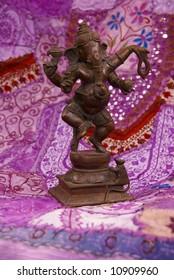 Bronze Ganesha dancing, on purple Rajasthani textile backdrop made from saris.