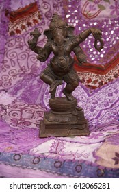 Bronze Ganesha dancing, on purple Rajasthani textile backdrop made from saris.  [Ganesha, the son of Shiva and Parvati, the elephant headed god,  is worshipped as the lord of beginnings