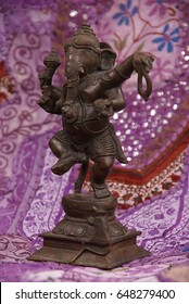 Bronze Ganesha dancing, on purple Rajasthani textile backdrop made from saris.  [Ganesha, the son of Shiva and Parvati, the elephant headed god,