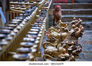 Bronze garuda statues and metal candlesticks on the fence in Dakshinkali hindu temple in Pharping, Nepal