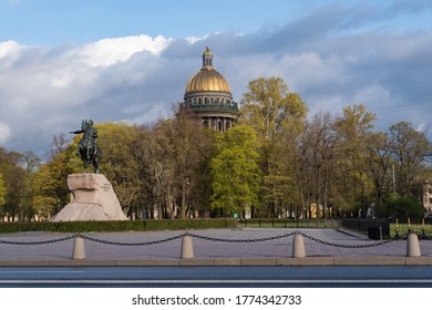 The Bronze Horseman is an equestrian statue of Peter the Great in the Senate Square.  Gold dome of St. Isaac's Cathedral at the background. Saint Petersburg, Russia