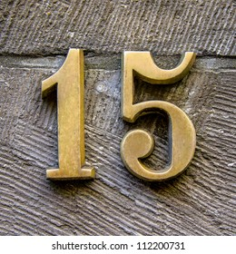 bronze house number fifteen on a stone background