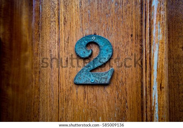 Bronze house number two (2)  on a wooden door