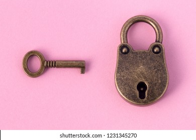 bronze key and padlock on gently pink paper, background image