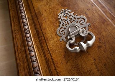 Bronze knocker on a stylish wooden door