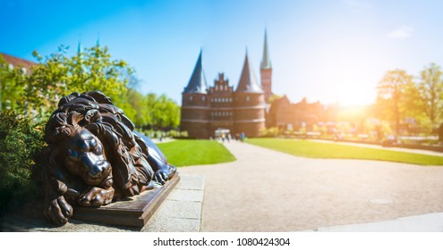 Bronze Lion statue in front of Holsten Gate - Panoramic shot of Holstentor and park, a city gate marking off the western boundary of the old center of Luebeck in Schleswig-Holstein, northern Germany