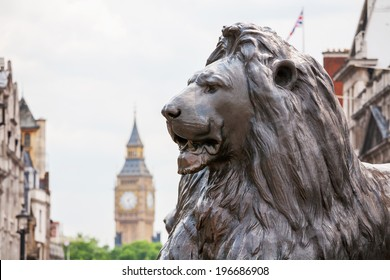 Bronze lion in Trafalgar Square with Big Ben in the background. London, England