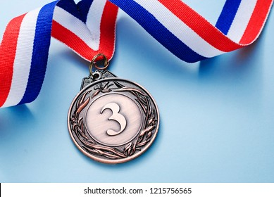 Bronze medal 3 place with a ribbon on a light blue background, the concept of victory or success