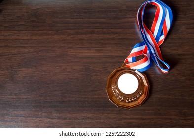 Bronze medal on wooden desk background. Selective focus. - Image