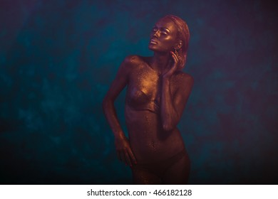 Bronze model touches her hair delicately while posing on the blue background