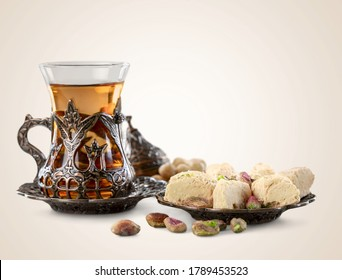 Bronze plate with arabic sweets and tea cups on the desk