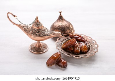 Bronze plate with dates and aladdin lamp on a white wooden background. Ramadan background.
