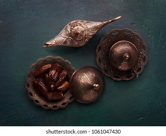 Bronze plate with dates, coffee cup and aladdin lamp on dark green wooden background. Ramadan kareem. Flat lay.