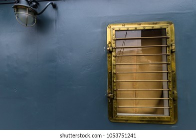 Bronze porthole of the ship on a gray background
