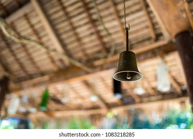 Bronze ring bell hanged under the wooden roof.