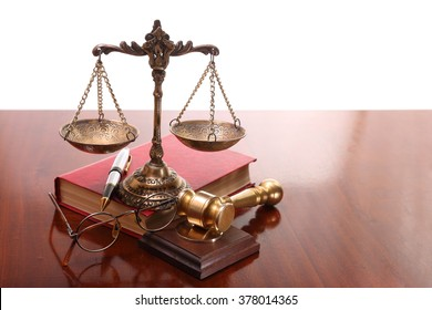 Bronze scales and gavel, glasses, pen and book on the table
