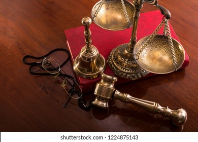 Bronze scales,gavel, bell, book and glasses on the table