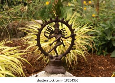 Bronze Shiva in garden, with blades of grass.   Nataraja