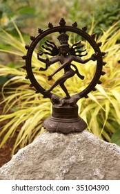 Bronze Shiva in garden, with blades of grass.   Nataraja (Sanskrit: Lord of Dance) Shiva