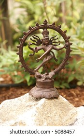 Bronze Shiva in garden, with blades of grass.   Nataraja (Sanskrit: Lord of Dance) Shiva represents apocalypse and creation as he dances away the illusory world of Maya  .