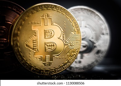 Bronze, silver and gold bitcoin coins close up.