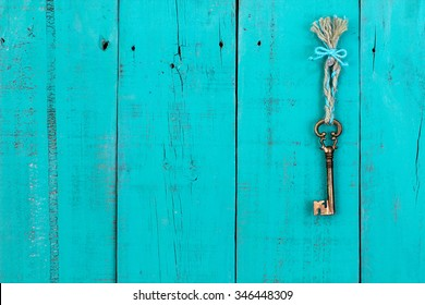 Bronze skeleton house key hanging by braided rope with turquoise ribbon on blank antique teal blue rustic wood door; home, security and real estate background with wooden painted copy space