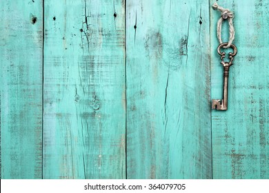 Bronze skeleton house key hanging by rope on blank antique mint green rustic wood door; real estate background with wooden painted copy space