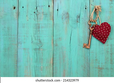 Bronze skeleton house key and red country fabric heart with stars hanging on antique teal blue old wood door; Valentines Day, real estate and home concept background with wooden painted copy space