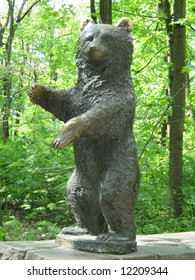 Bronze standing bear statue with reflection in nature