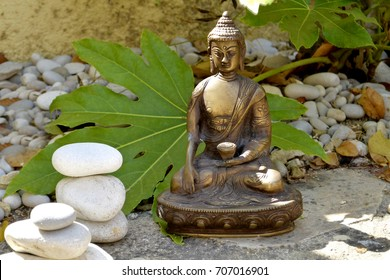 Bronze statue of Buddha touching Earth with White flowers in the garden and balanced stones
