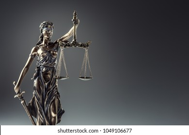 Bronze statue Lady Justice holding scales and sword.